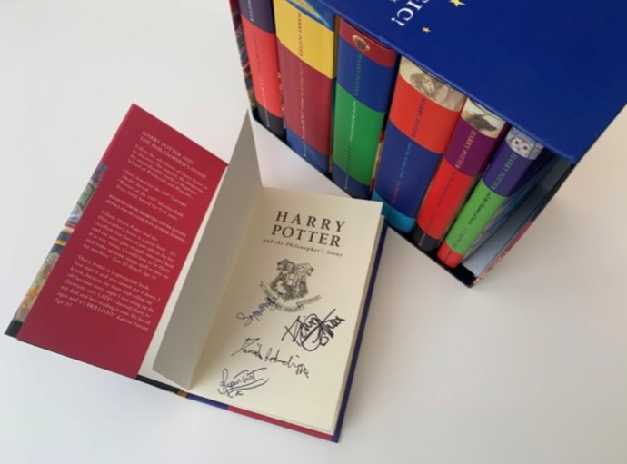 Full boxed set of the Harry Potter children's books by J.K. Rowling, all first editions signed by Daniel Radcliffe, Rupert Grint, Emma Watson, and Robbie Coltrane